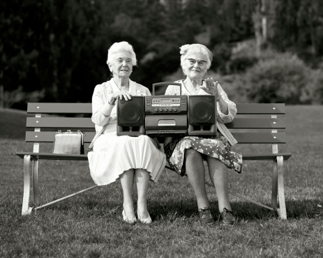 Women sitting on park bench holding stereo boombox